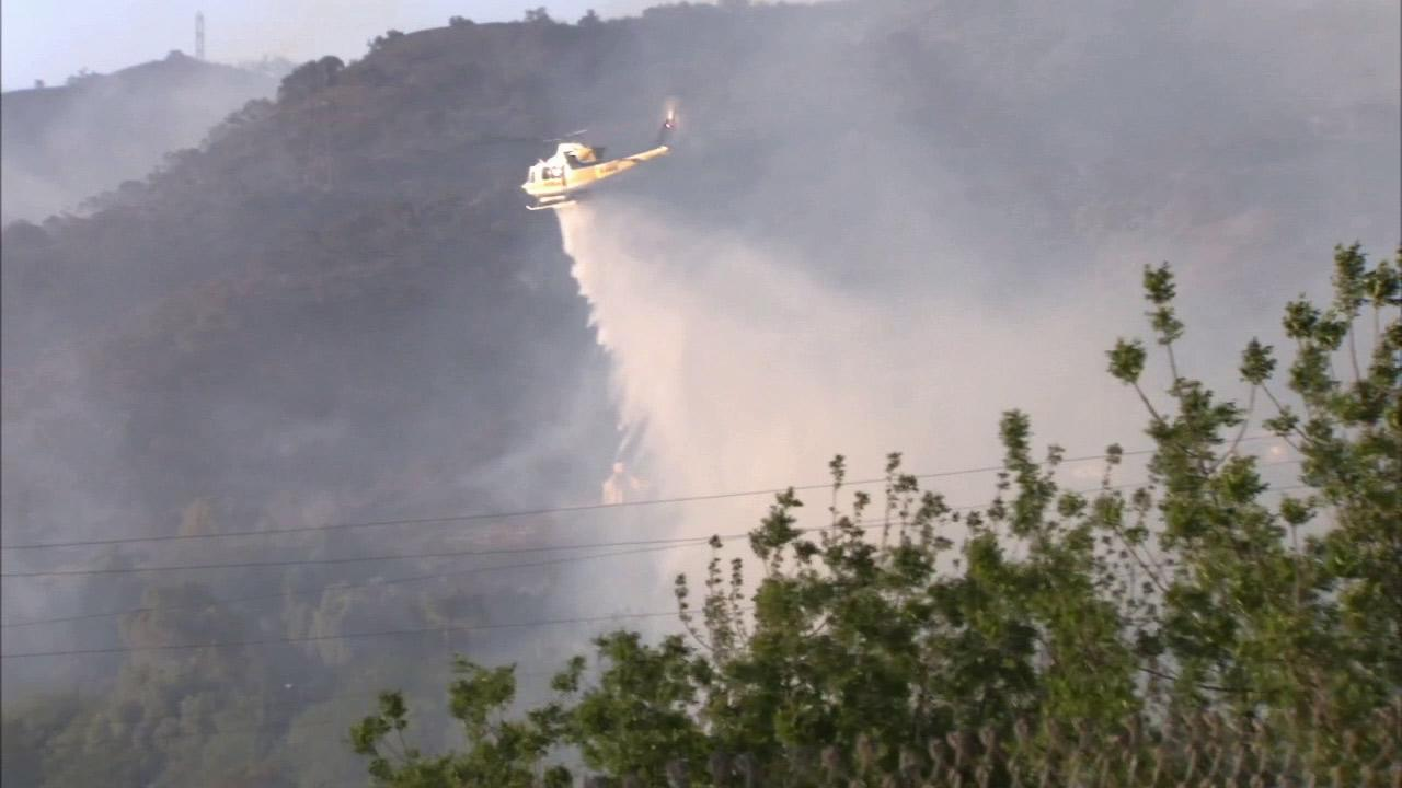 A helicopter makes a water drop above a brush fire burning in the hills of Fillmore on Monday, April 8, 2013.