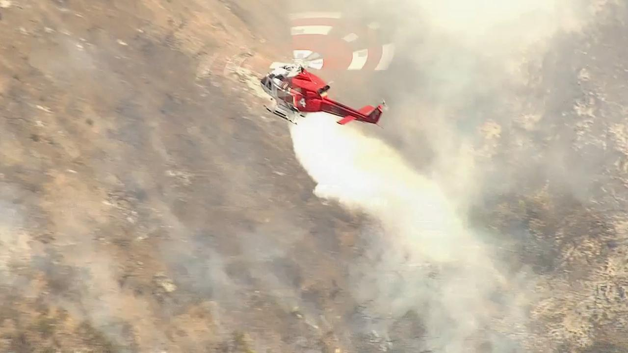A helicopter douses a fire that erupted in Glendale on Friday, May 3, 2013.