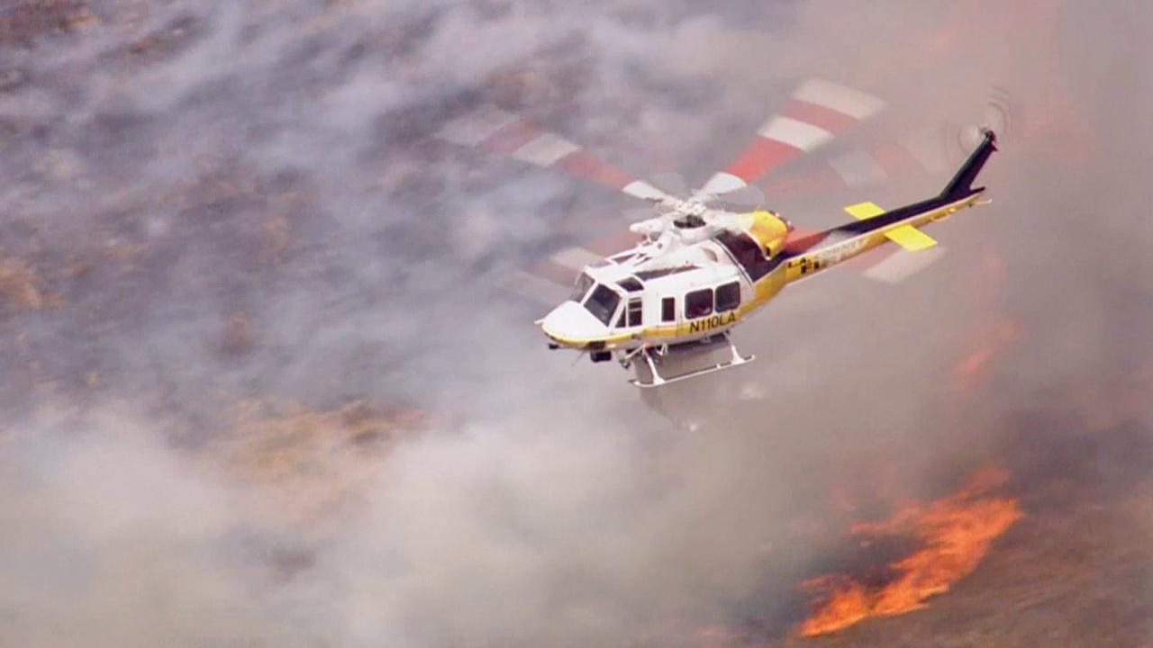 A helicopter aids in the firefight after a brush fire erupted in Castaic on Friday, May 17, 2013.