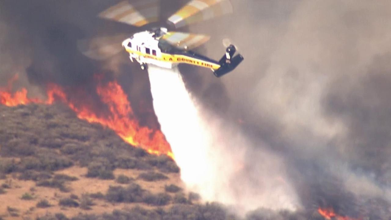 A helicopter aids in the firefight after a brush fire broke out in the Castaic area on Friday, May 17, 2013.