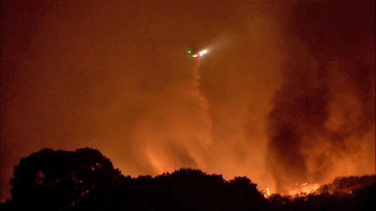 An aircraft makes a water drop as the Powerhouse Fire continues to burn in the Angeles National Forest north of Santa Clarita on Saturday, June 1, 2013.