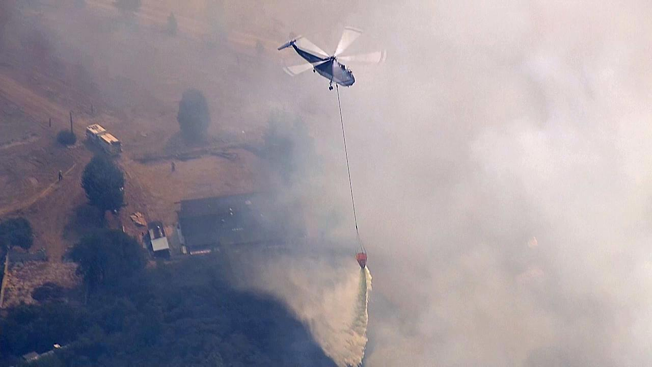 An aircraft makes a water drop on the Powerhouse Fire, which continued to burn in the Angeles National Forest north of Santa Clarita on Sunday, June 2, 2013.
