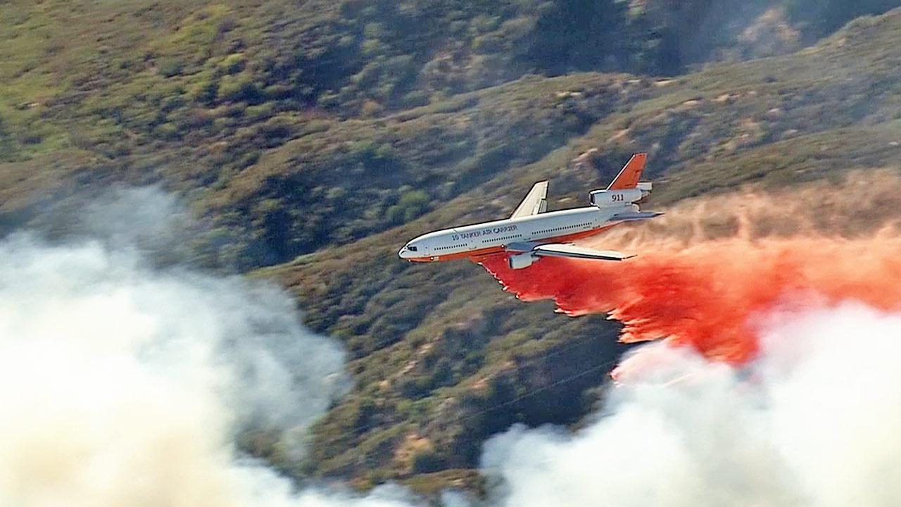 An aircraft drops fire retardant over a fire burning in the San Bernardino Mountains on Tuesday, Sept. 24, 2013.