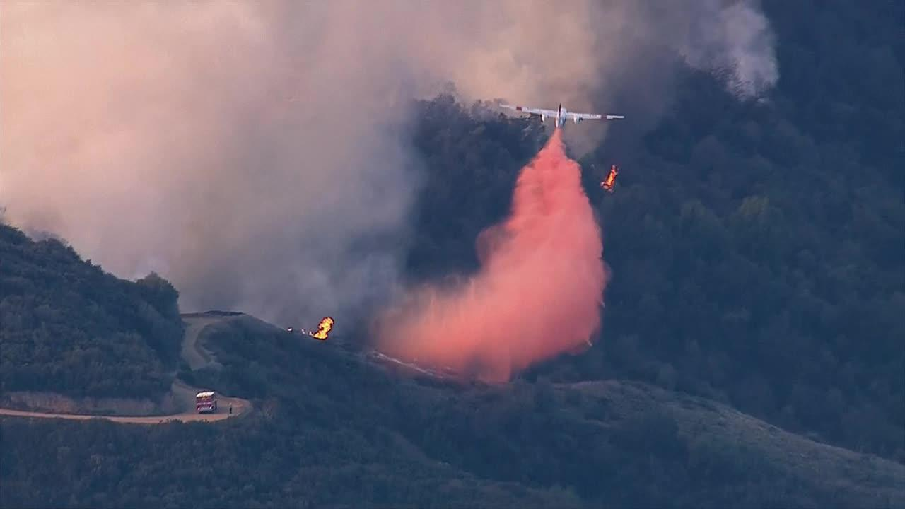 A plane drops fire retardant on a fast-moving brush fire that erupted in the foothills above Glendora on Thursday, Jan. 16, 2014.