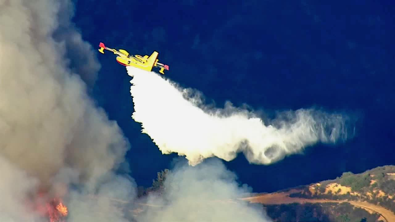 A Super Scooper plane drops water on a fast-moving brush fire that erupted in the foothills above Glendora on Thursday, Jan. 16, 2014.