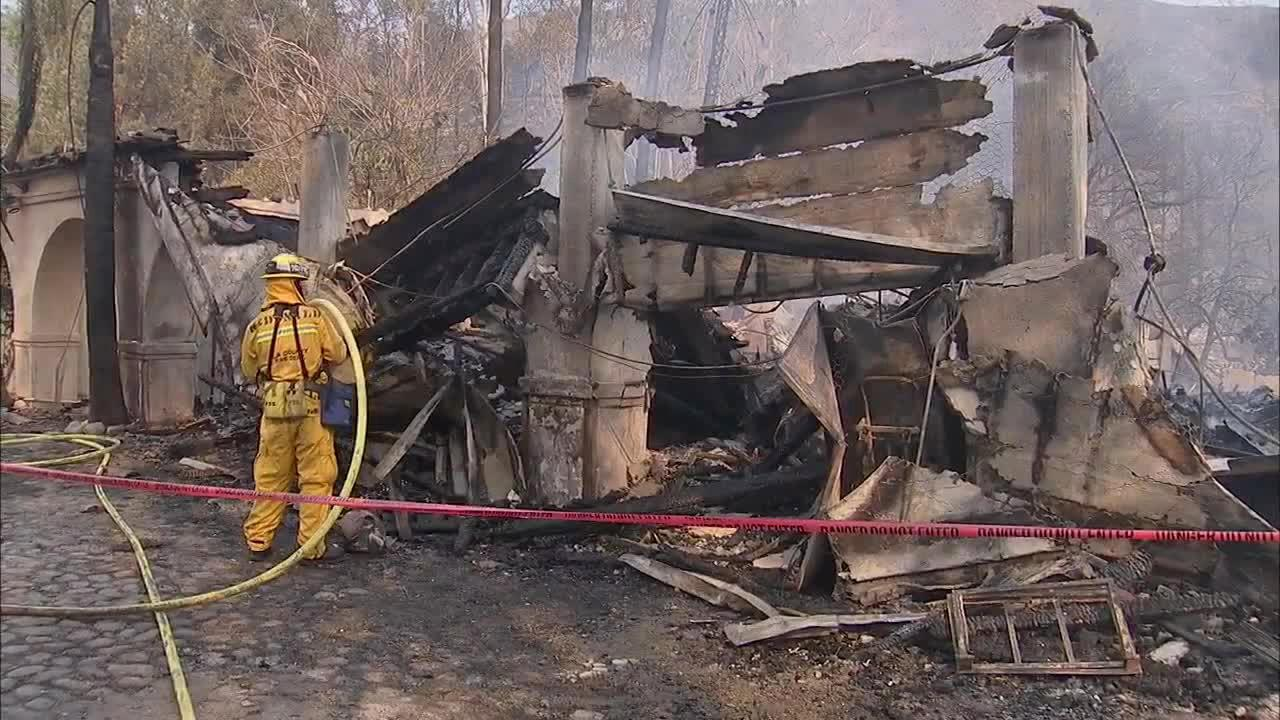 Firefighters are seen dousing flames on this house on Kremont Drive that was destroyed by a brush fire burning in the foothills above the Glendora and Azusa area on Thursday, Jan. 16, 2014.