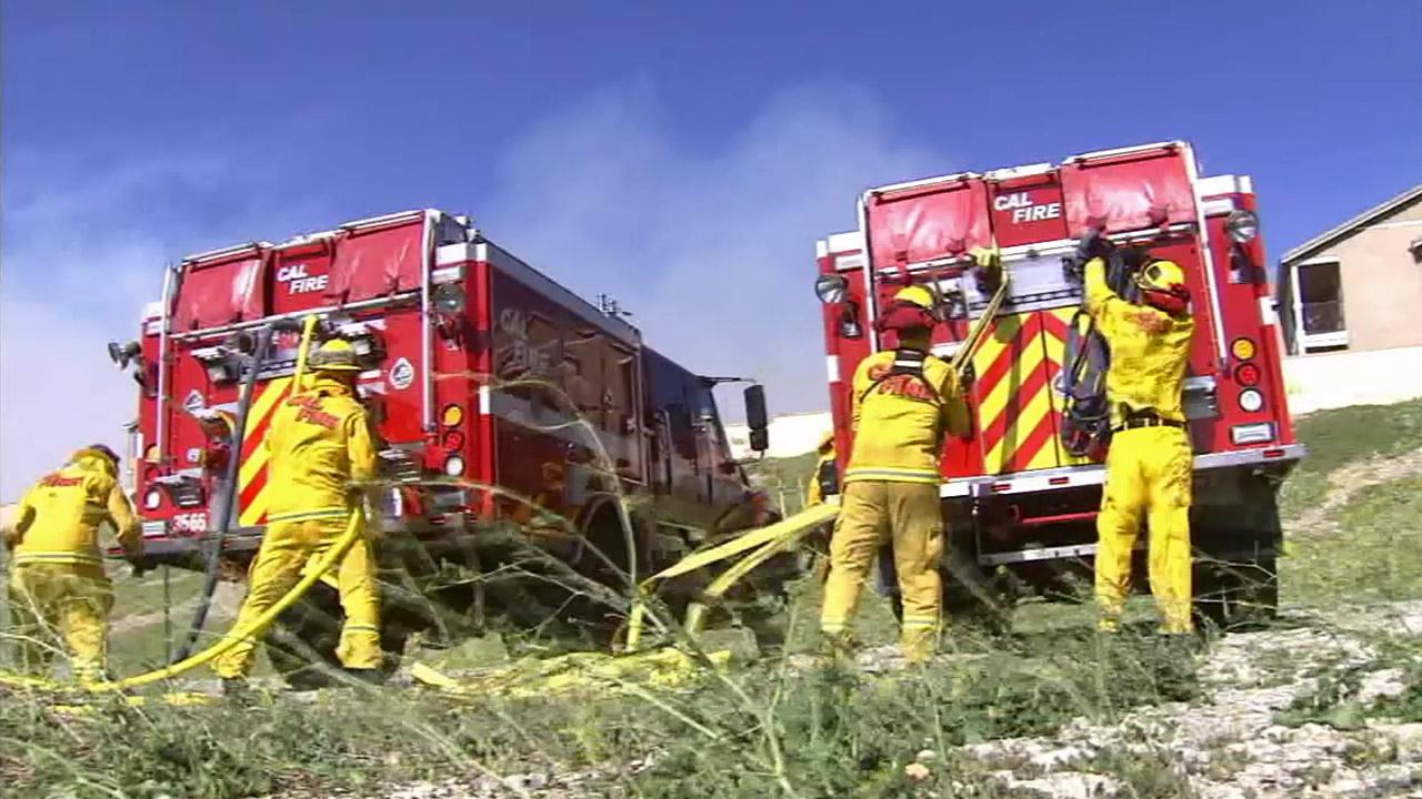 Firefighters work to put out a brush fire near Rancho Cucamonga under hot and windy conditions Wednesday, April 30, 2014.