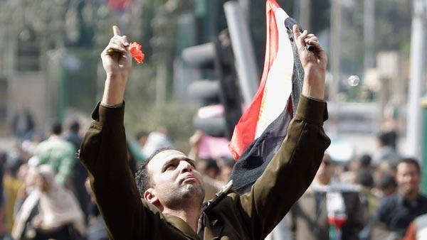 A man identified only as Fathi, wearing the uniform of a captain in the Egyptian army, is carried by demonstrators on Tahrir, or Liberation Square, in Cairo, Egypt, Monday Jan. 31, 2011.