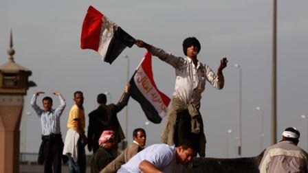 An anti-government protester swings an Egyptian flag, while smoking a cigarette, to beckon others to reinforce those at the frontline of clashes with pro-government supporters, near the Egyptian Museum in downtown Cairo
