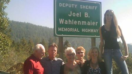 The Wahlenmaier family at the real dedication sign on Highway 168.