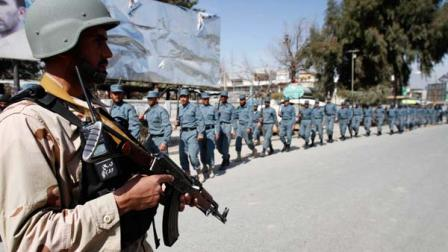 Afghan policemen march towards an anti-U.S. demonstration in Mehterlam, Laghman province east of Kabul, Afghanistan, Saturday, Feb. 25, 2012.