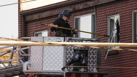 Police break out a window of an apartment where the suspect in a shooting at a movie theatre lived in Aurora, Colo., Friday, July 20, 2012.