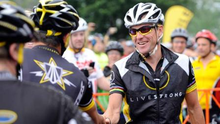 Cyclist Lance Armstrong greets fellow riders