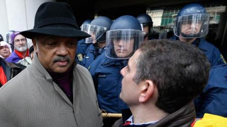 Rev. Jesse Jackson, left, and Lansing Mayor Virg Bernero, right, try to enter past Michigan State Police at the George W. Romney State Building, where Gov. Snyder has an office in Lansing, Mich., Tuesday, Dec. 11, 2012.