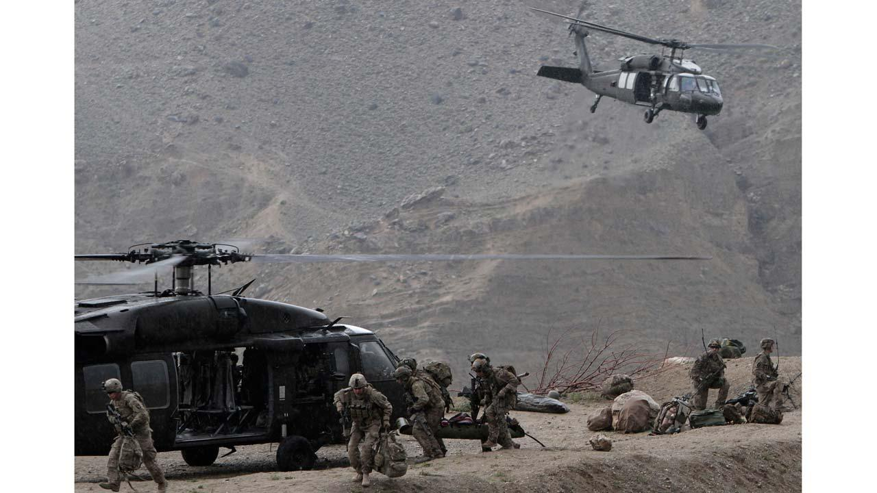 U.S. Black Hawk helicopters arrive to the scene after a NATO helicopter crashed in a field killing two American service members, near Gerakhel, eastern Afghanistan, Tuesday, April 9, 2013.