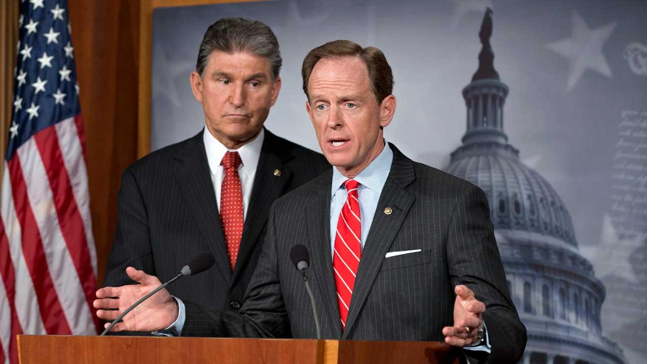 Democratic Sen. Joe Manchin of West Virginia, left, and Republican Sen. Patrick Toomey of Pennsylvania, right, announce that they have reached a bipartisan deal on expanding background checks to more gun buyers