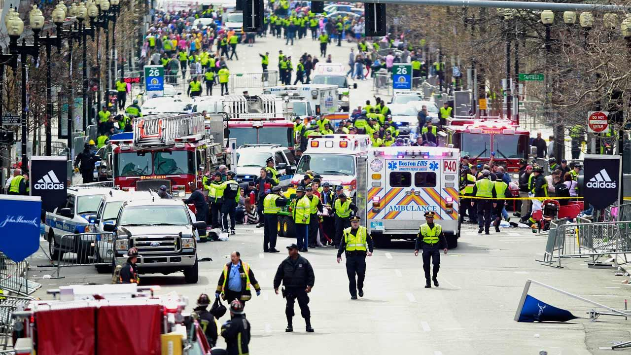 Police clear the area at the finish line of the 2013 Boston Marathon as medical workers help injured following explosions in Boston, Monday, April 15, 2013.