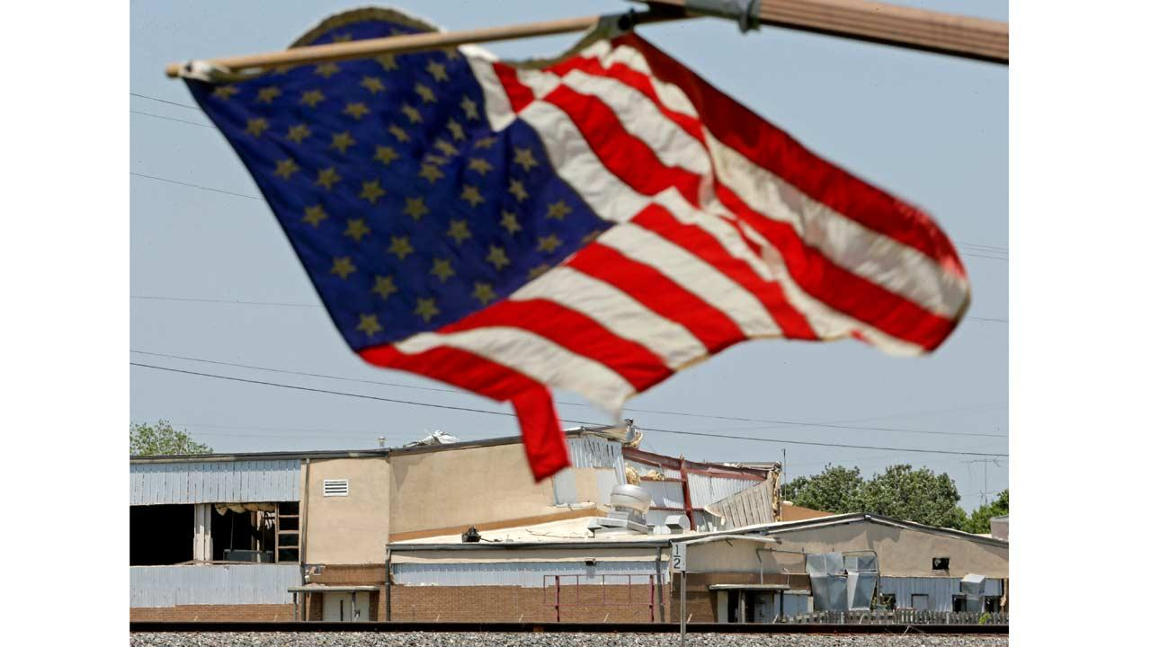 Five days after a fertilizer plant explosion, a flag flies from a damaged home as the damaged West Intermediate School is seen in the distance Monday, April 22, 2013, in West, Texas.