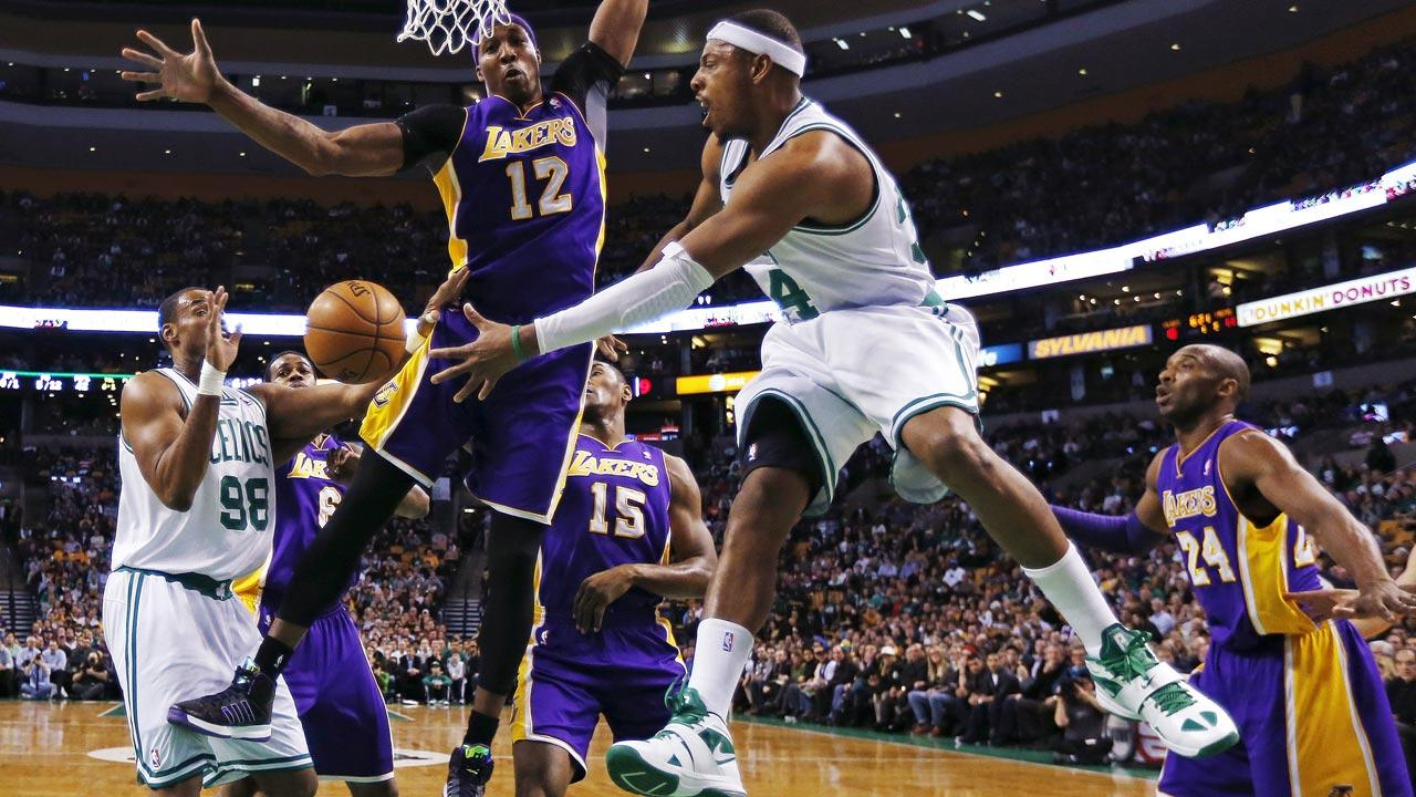 Boston Celtics forward Paul Pierce (34) dumps off the ball to center Jason Collins (98) as he is pressured by Los Angeles Lakers center Dwight Howard (12) during the first quarter of an NBA basketball game in Boston