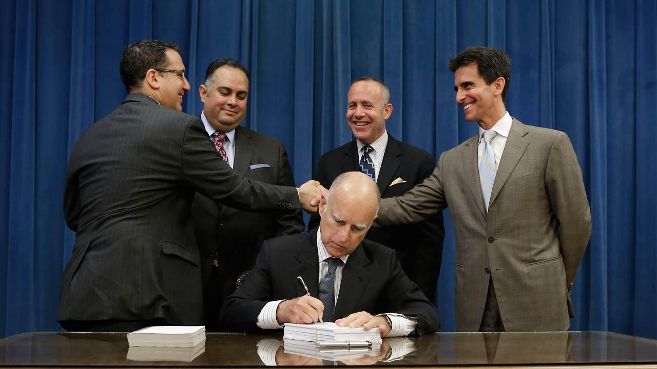 Gov. Jerry Brown signs the state budget at the Capitol Thursday