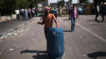 A supporter of ousted Egyptian President Mohammed Morsi stands on guard armed with a stick and a shield during a protest at Cairo University, Giza, Egypt, Friday, July 5, 2013.