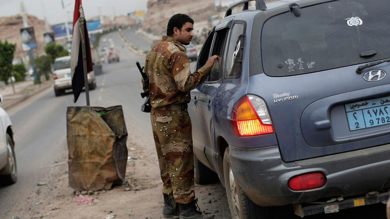 A Yemeni soldier inspects a car at a checkpoint on a street leading to the U.S. embassy in Sanaa, Yemen