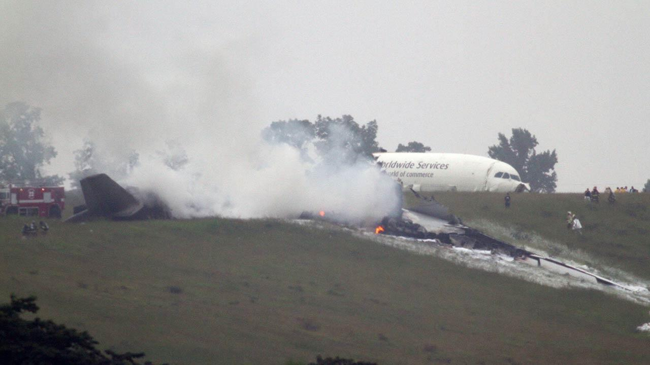 Debris burns as a UPS cargo plane lies on a hill at Birmingham-Shuttlesworth International Airport after crashing on approach, Wednesday, Aug. 14, 2013, in Birmingham, Ala.