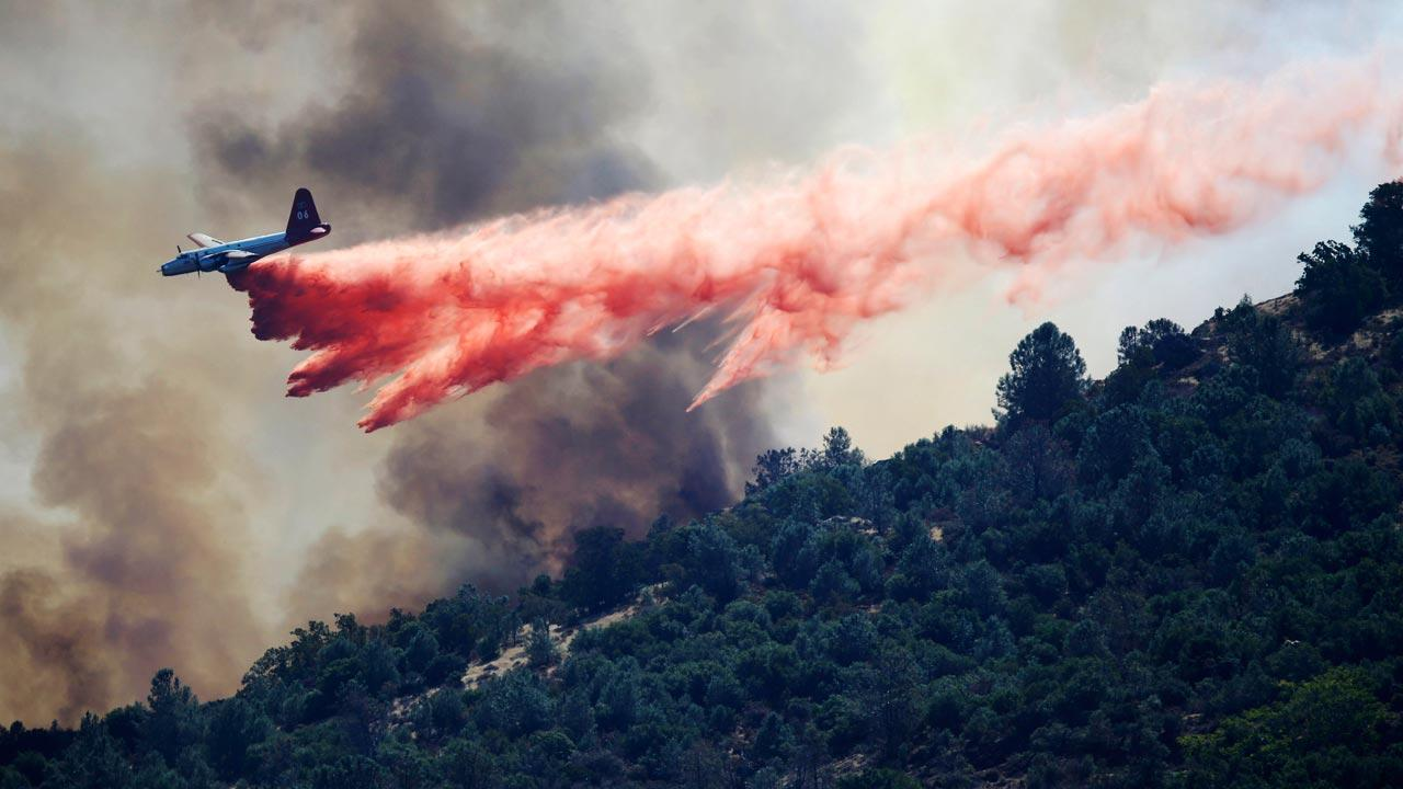 A bomber drops retardant on a wildfire in Mount Diablo State Park on Monday, Sept. 9, 2013 in Contra Costa County, Calif. A wildfire burning outside Mount Diablo State Park has forced dozens of residents and animals to evacuate Monday.