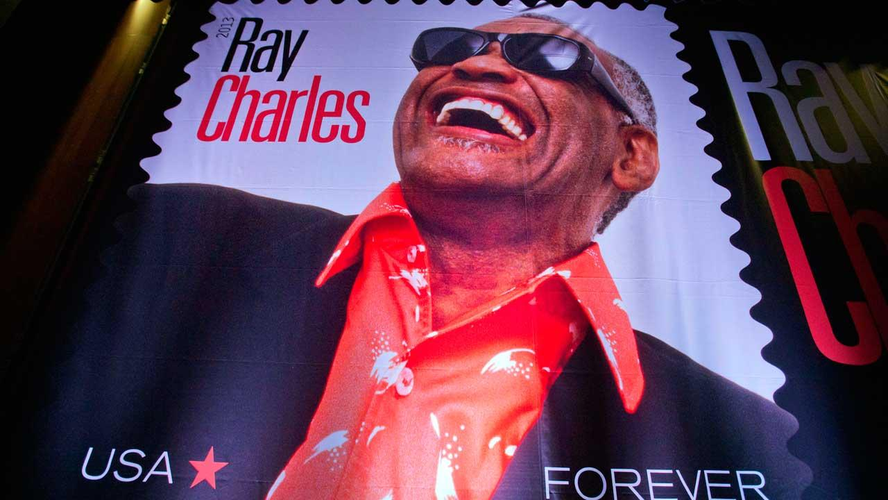 A stamp featuring musician Ray Charles hangs backstage before its unveiling an event at Morehouse College in Atlanta, Monday, Sept. 23, 2013. The U.S. Postal Service is planning to add soul singer Ray Charles to its Music Icons Forever stamp series.