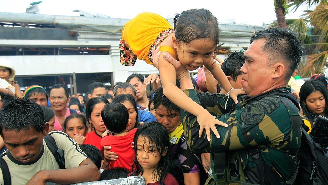 Philippine military personnel try to prioritize children and women first as people wait for evacuation flights in Tacloban, central Philippines