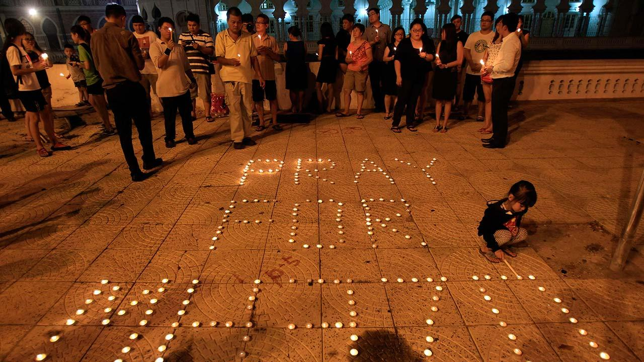 A girl lights a candle next to a message reading Pray for MH370 during a candlelight vigil