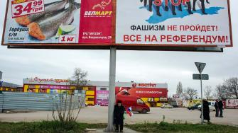 An elderly man holds a Russian flag as he stands at an advertising hoarding, the right part of which reads Fascism wont succeed. Everybody to the referendum!
