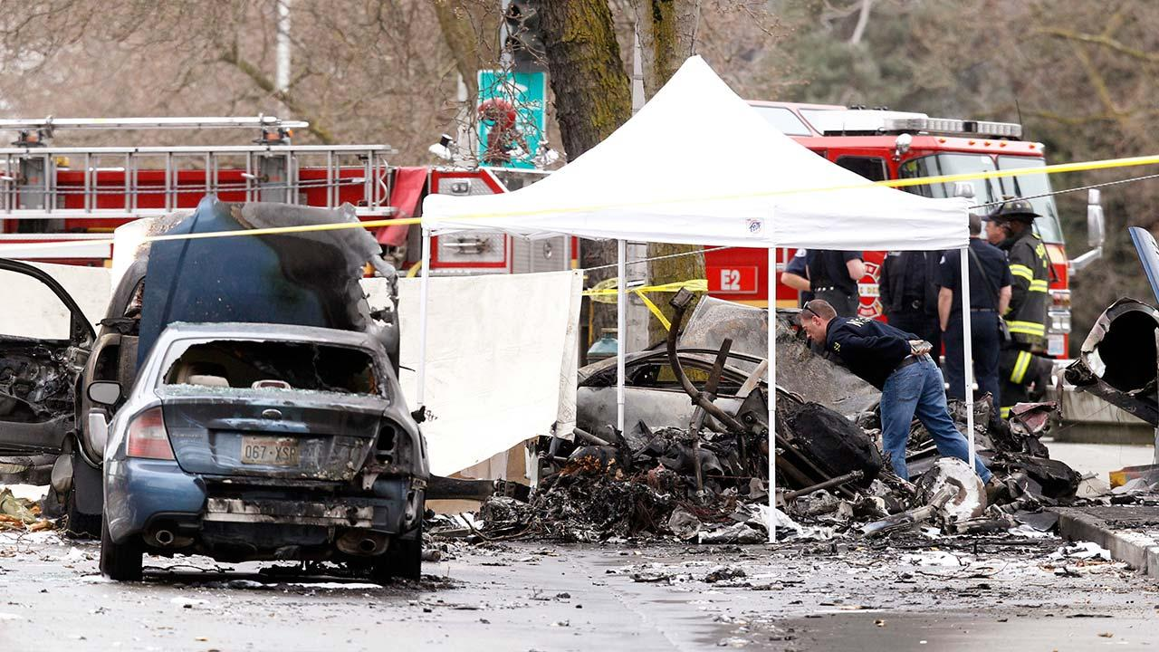 An investigator looks over the charred wreckage of a news helicopter and two vehicles after the chopper crashed into a city street near the Space Needle, Tuesday, March 18, 2014, in Seattle. Two people were killed and another critically injured.