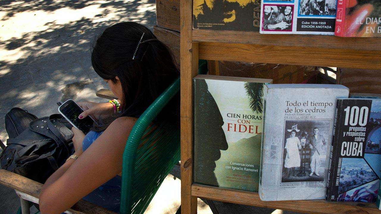 A book street vendor passes the time on her smart phone as she waits for customers in Havana, Cuba, Tuesday, April 1, 2014.