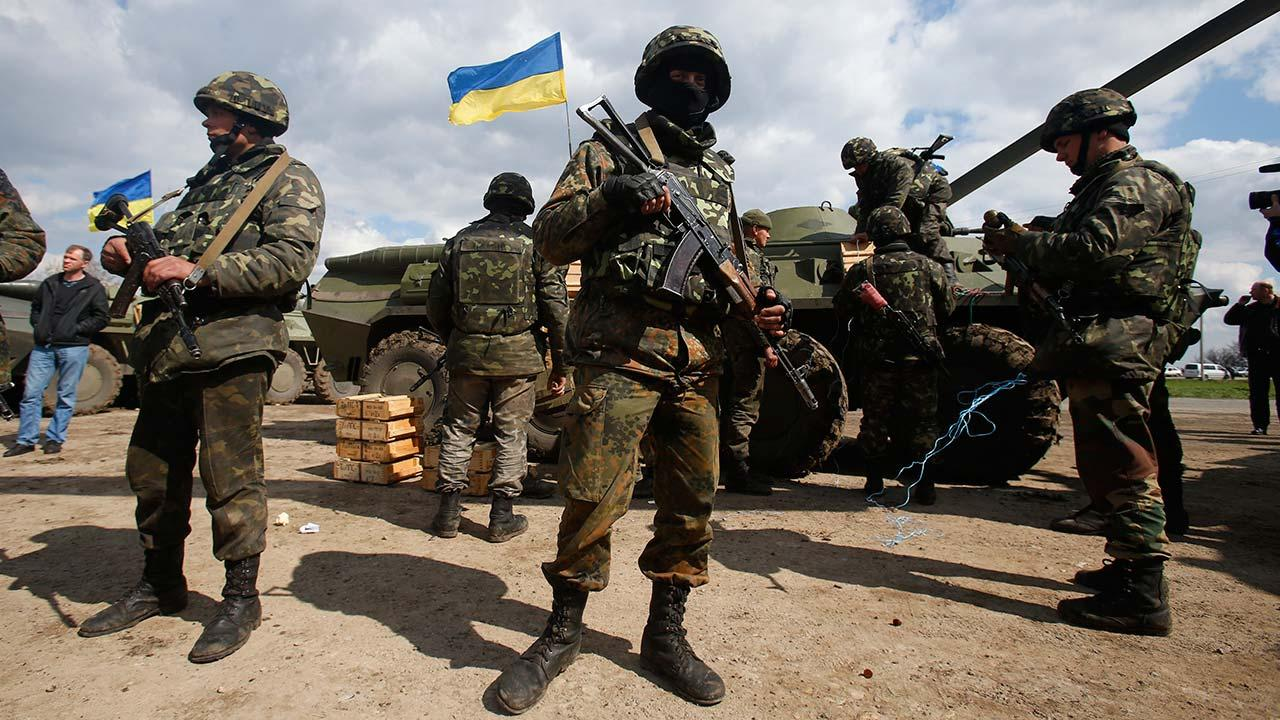 Ukrainian army troops receive ammunition, with a Ukrainian flag in the back, in a field on the outskirts of Izyum, Eastern Ukraine, Tuesday, April 15, 2014.