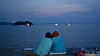 Relatives of passengers aboard the sunken ferry Sewol sit near the sea at a port in Jindo, south of Seoul, South Korea, Sunday, April 20, 2014.