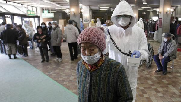 A woman is scanned for radiation exposure at a temporary scanning center for residents living close to the quake-damaged Fukushima Dai-ichi nuclear power plant