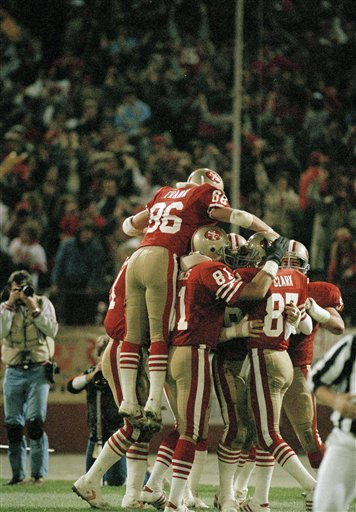 San Francisco 49ers John Frank &#40;86&#41; leaps high above a group of 49ers that rushed to congratulate Dwight Clark &#40;87&#41; after he scored a touchdown in the fourth quarter against Seattle in Candlestick Park in San Francisco, Nov. 26, 1985. Clark&#39;s touchdown established a team record for career receptions when he caught a 22-yard pass from Joe Montana. The 49ers defeated Seattle, 19-6. <span class=meta>(AP Photo&#47;Paul Sakuma)</span>