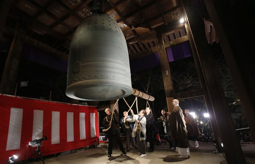 Japan New Year&#39;s Eve - People strike a giant bell to celebrate the New Year at Zojoji Buddhist temple, in Tokyo, early Wednesday, Jan. 1, 2014. <span class=meta>(AP Photo&#47;Shizuo Kambayashi)</span>