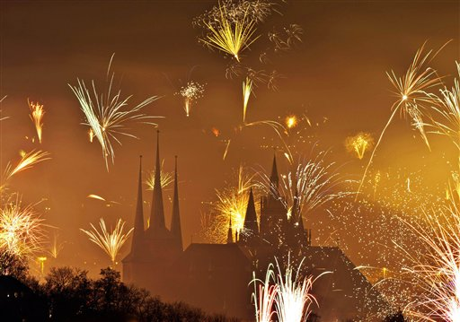 Germany New Year&#39;s Eve - Fireworks light the sky above the Mariendom &#40;Cathedral of Mary&#41;, right, and the St. Severi&#39;s Church, left, shortly after midnight during New Year&#39;s Eve celebrations in Erfurt, central Germany, Wednesday, Jan 1, 2014. <span class=meta>(AP Photo&#47;Jens Meyer)</span>