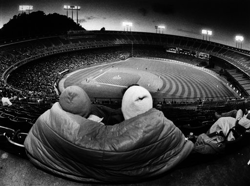 Two women take shelter from the cold with a sleeping bag on the upper deck of Candlestick Park in San Francisco, July 9, 1985. This season, the Giants have moved most of their games to midday because too few fans were willing to brave the cold summer nights at the park. <span class=meta>(AP Photo&#47;Eric Risberg)</span>