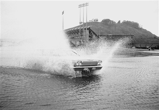 An automobile throws up a big spray as it drives through the parking lot at Candlestick Park in San Francisco where the sixth game of the World Series was canceled by heavy rains resulting from storm moving across northern California, Oct. 13, 1962. The stands are almost obscured by the heavy spray.  <span class=meta>(AP Photo)</span>