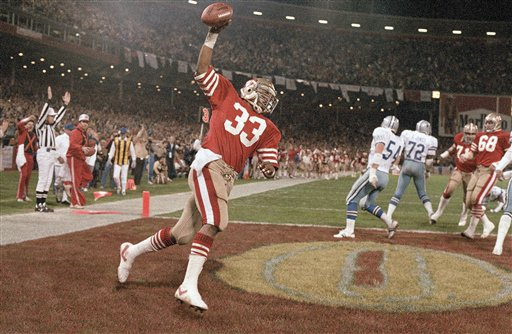 Roger Craig #33 runs with the ball push in the air after scoring a touchdown early in the first quarter against the Dallas cowboys in Candlestick Park, San Francisco on Monday, Dec. 20, 1983. Craig second two touchdowns in the 49ers 42-17 win that gave them the NGC west title. <span class=meta>(AP Photo&#47;Eric Risberg)</span>