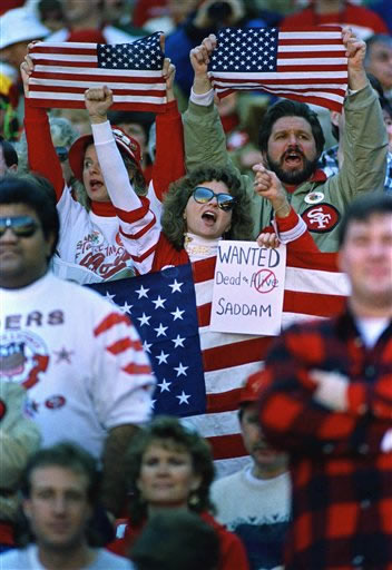 Fans in the crowd at Candlestick Park in San Francisco Sunday, Jan. 20, 1991 display American flags and anti-Hussein sign before the 49ers met the New York Giants in the NFC championship game. <span class=meta>(AP Photo&#47;Eric Risberg)</span>