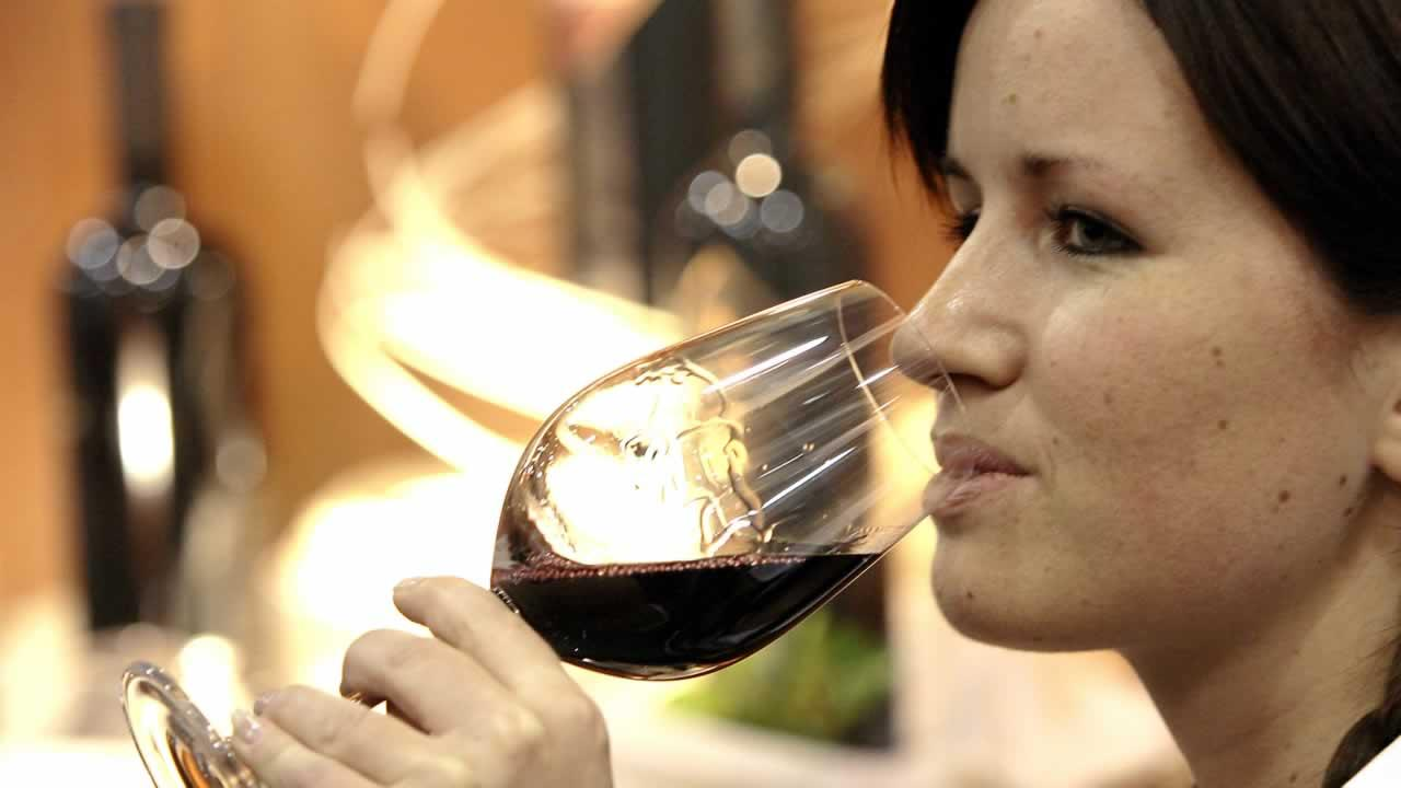 A woman drinking a glass of red wine.