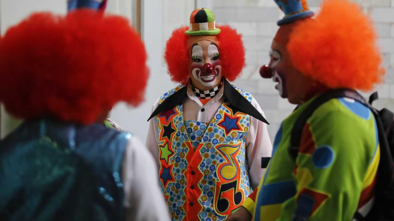In this Monday, Oct. 21, 2013 photo, clowns chat after registering to attend the 17th International Clown Convention in Mexico City.