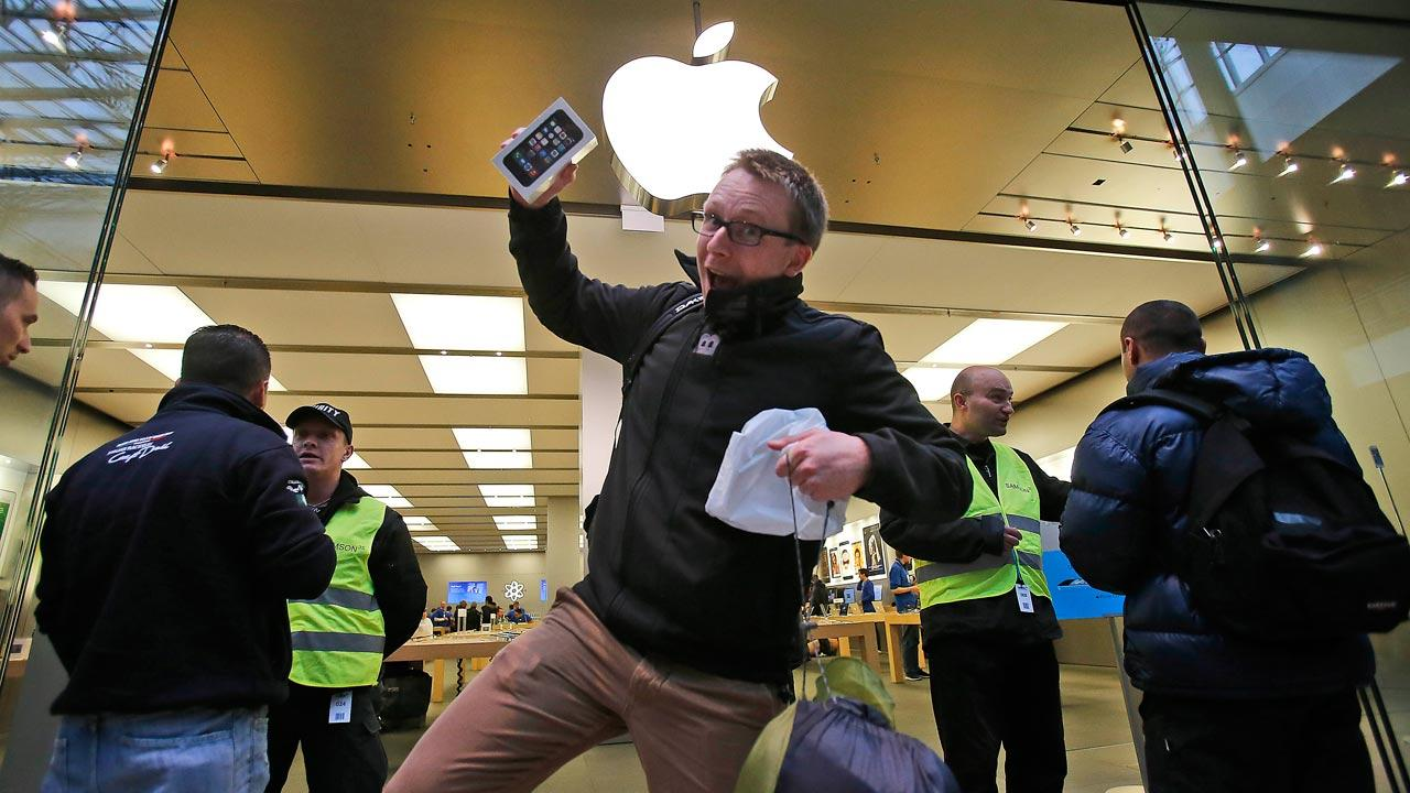 A customer of the Apple store in Oberhausen celebrates with the new iPhone 5S as he leaves the store at the start of the new iPhone sale in Oberhausen, Germany, Friday, Sept. 20, 2013. (AP Photo/Frank Augstein)