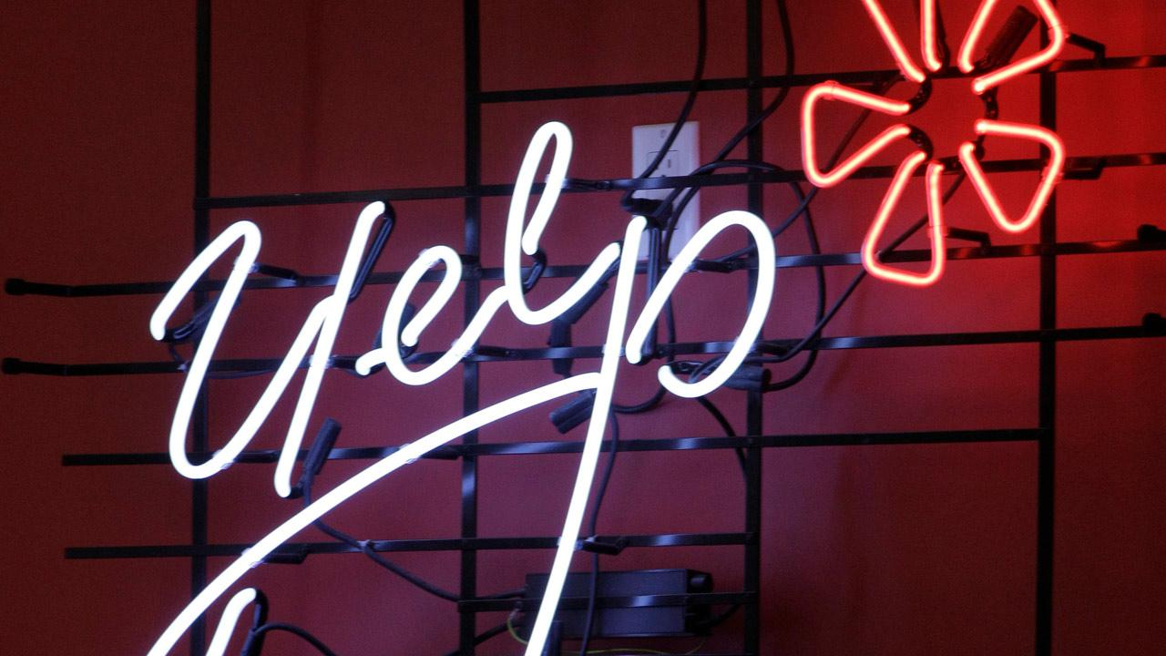 Yelps corporate logo is shown in neon at the opening of Manhattan offices of the online reviews website in New York, Wednesday, Oct. 26, 2011. (AP Photo/Kathy Willens)