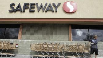 In this Feb. 23, 2011 file photo, a customer grabs a shopping cart at a Safeway store in Cupertino, Calif.