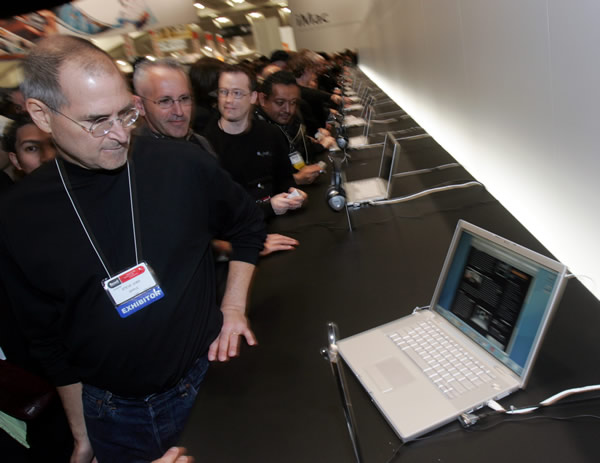 Apple Computer Inc. CEO Steve Jobs looks at the new Apple MacBook Pro laptop on the showroom floor at the MacWorld conference in San Francisco, Tuesday, Jan. 10, 2006. Apple Computer Inc.&#39;s historic shift to Intel Corp. microprocessors came months earlier than expected Tuesday as Jobs unveiled desktop and notebook computers based on new two-brained chips from the world&#39;s largest semiconductor company&#39;s. <span class=meta>(AP Photo&#47;Paul Sakuma)</span>